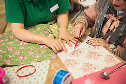 Senior woman with nurse making rabbit shape on fabric during Easter at rest home