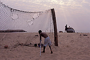 A boy with polio plays as goalkeeper and retrieves the ball from the net on Luanda's beach, Angola.