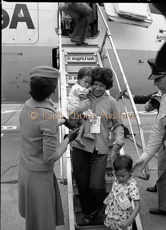 Vietnamese Refugees Arrive In Ireland.   (M85)..1979..09.08.1979..08.09.1979..9th August 1979..As part of an UNHCR initiative, Ireland agreed to take some of the Vietnamese (boat people) refugees into the country. A temporary refugee centre has been set up in the grounds of Blanchardstown Hospital to accomodate the families, from where they will be assimilated into the community..Image shows a happy Vietnamese mother with her bewildered children disembarking from the Aer Lingus aircraft.