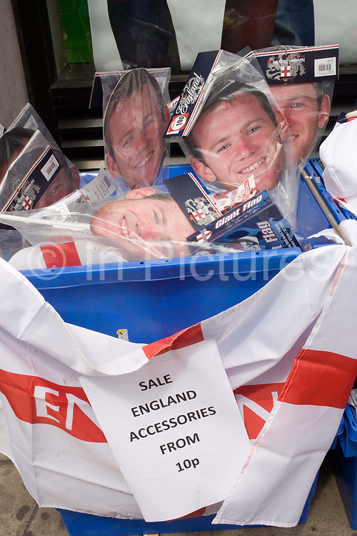 The England footballer Wayne Rooney's faces are seen wrapped up in polythene, sold outside a shop near St. Paul's Cathedral where merchandise accessories are being sold off cheap outside sports shop in City of London. It is a few days after the England team's defeat by Germany in the quarter-finals of the South African World Cup and while English flags are stored away in time for the next St. George's Day when nationalism and patriotic emotions are showed on homes, in streets and on working mans' vans, these Rooney face masks are now seen as passé, unsellable at current prices so their value has been reduced from just 10 pence. Golden boy Rooney is still a commodity that Manchester United earn millions from – their merchandising opportunities reach a fever levels at times of premiership and international matches.