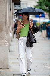 © Licensed to London News Pictures. 27/07/2021. LONDON, UK.  A woman out shopping in Regent Street.  According to new analyis by Huq Industries, a mobility research business, the UK's Covid app 'pingdemic' is leading to a significant slowdown in people both moving around and visiting shops. Across the UK as a whole in July, average retail footfall has fallen by 2.83% and mobility by 5.5%.  Photo credit: Stephen Chung/LNP