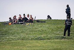 © Licensed to London News Pictures. 13/04/2020. London, UK. Camden council workers move a group of women sitting down having their lunch on top of Primrose Hill in London, during a pandemic outbreak of the Coronavirus COVID-19 disease. The public have been told they can only leave their homes when absolutely essential, in an attempt to fight the spread of coronavirus COVID-19 disease. Photo credit: Ben Cawthra/LNP