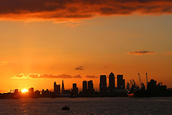 LNP Weekly Highlights 28/03/14  © Licensed to London News Pictures. 23/03/2014. The sun sets over the Thames today, casting Canary Wharf and the Shard into silhouette. Credit : Rob Powell/LNP