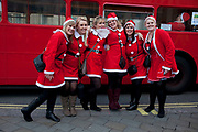 London, UK. Sunday 9th December 2012. A flash mob of Santas descends on Trafalgar Square arriving on Routemaster buses. Christmas celebrated here with the annual Santa Pub Crawl party visiting the famous pubs & sights of London with everyone decked out in jolly red Santa suits. Organised by Fanatics, an Australian sports and party company.