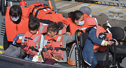 © Licensed to London News Pictures. 18/09/2021. Dover, UK.  Border force officials assist migrants as they arrive at Dover Harbour in Kent. Migrants are continuing to attempt the crossing from France as the weather improves this week. Photo credit: Stuart Brock/LNP