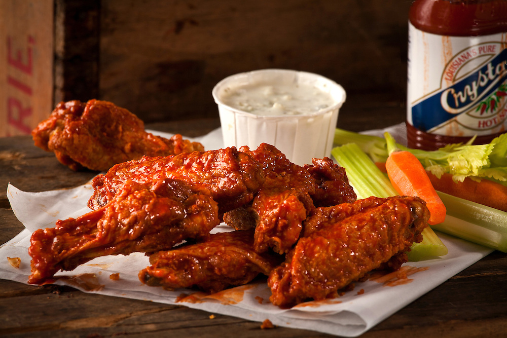 Fried Chicken wings,with barbeque sauce,blue cheese dressing,celery,and hot sauce on wooden crate
