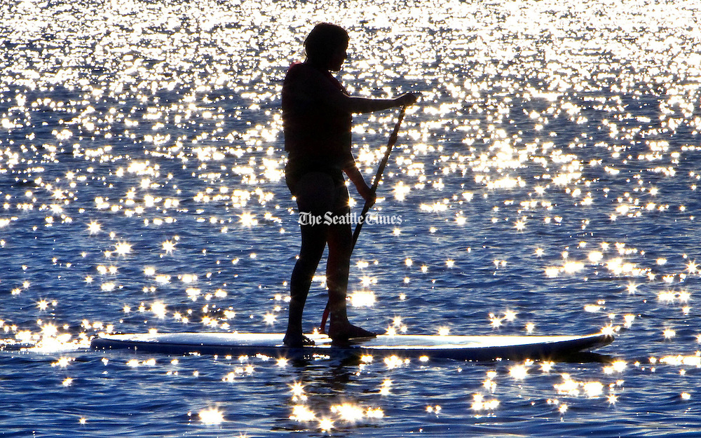 A paddleboarder makes her way across a sparkling Green Lake as the sun begins to set behind the lake. (Mike Siegel / The Seattle Times)