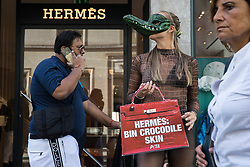 A PETA supporter wearing a Venetian crocodile mask poses outside the Hermès store in New Bond Street in protest against the luxury fashion house's use of exotic skins on 8th September 2021 in London, United Kingdom. PETA's campaign was launched following the release of video footage by The Kindness Project showing crocodiles being mutilated, electrocuted, stabbed and shot on farms in Australia with ties to Hermès and PETA are calling on the fashion brand to cease using exotic skins for their products.