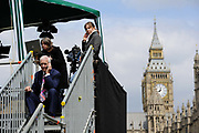 Television journalist Jon Snow (L) and other members of the T.V. media make calls on their mobile phones in a make shift structure opposite The House of Parliament during the 2010 British General Election.