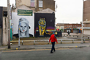 Man passing a graffiti wall painting by Otto Schade in East Topping street on 21st April 2021 in Blackpool, Lancashire, United Kingdom. The work was made in 2016 for the Sun, Spray and Art, Blackpools Urban Art Festival.
