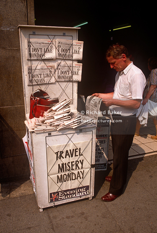 A Newspaper seller displays copies of the London tabloid aimed at commuters The Evening Standard, on sale here at Monument underground station. On this day, the headline is about the tube and rail strike that inconvenienced thousands of Londoners on 21st June 1989. Passengers who might have descended into the subterranean tunnels of this Victorian transport system, purchase their favoured paper containing all the news of the industrial action.