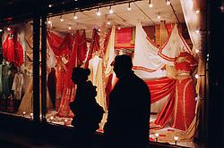 High street shop window displaying traditional saris and fabrics,