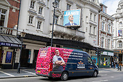 A food delivery van for 'Woods' passes beneath the Apollo Theatre where the last production before the Coronavirus lockdowns a year ago was the production, Jamie, on Shaftesbury Avenue in London's Theatreland, on 27th April 2021, in London, England.