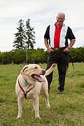 USA, Oregon, Keizer, a Labrador Retriever stands with her master in the dog park. MR