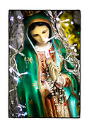 SHOT 2/20/19 10:03:57 AM -  A small freestanding capilla outside a food stall in Merida, Mexico. The capilla featured a statue of Our Lady of Guadalupe and various flowers. Passersby left pesos on the statue. Our Lady of Guadalupe is a powerful and ubiquitous symbol of Mexican identity because some guess that Our Lady of Guadalupe's skin tone matches that of Mexico's indigenous population: light brown. She is as much revered for her striking similarity to the vanquished native Mexican population as she is for being the mother of God. Mérida is the capital and largest city in Yucatan state in Mexico, as well as the largest city of the Yucatán Peninsula. As the largest city in the Yucatan it has become a hub for commerce and culture. (Photo by Marc Piscotty / © 2019)