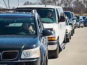 """20 MARCH 2020 - DES MOINES, IOWA: Motorists line up to get free hand sanitizer at The Foundry, a Des Moines distiller. The distillery suspended its distilling operations to make hand sanitizer this week. They distributed it free to people who came to their building. On Friday thousands of people came to get some. There line was more than one mile long. On Friday morning, 20 March, Iowa reported 45 confirmed cases of the Coronavirus. Restaurants, bars, movie theaters, places that draw crowds are closed for at least 30 days. There are no """"shelter in place"""" orders in effect anywhere in Iowa but people are being encouraged to practice """"social distancing"""" and many businesses are requiring or encouraging employees to telecommute.       PHOTO BY JACK KURTZ"""