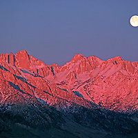 The moon sets at sunrise over the Sierra Nevada. Mount Whitney (L).