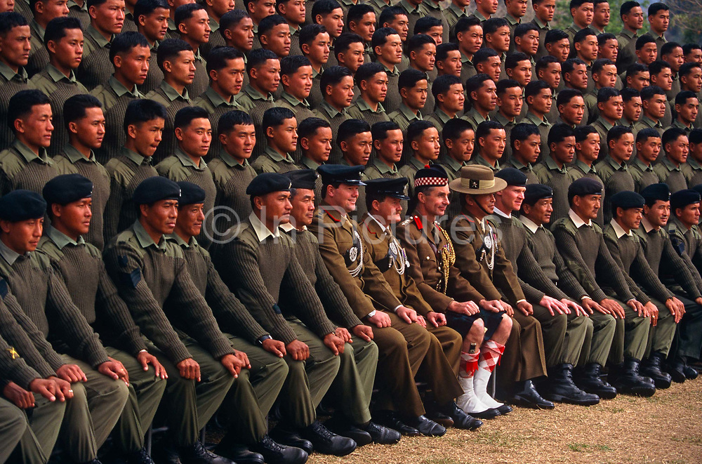 Officers and new recruits of the British Royal Gurkha Regiment pose for their official photograph at their army camp at Pokhara, Nepal after recently being recruited into the regiment after a gruelling series of tests to eliminate the weaker and less able candidates, before the 160 lucky candidates travel to the UK for basic training. 60,000 boys aged between 17-22 (or 25 for those educated enough to become clerks or communications specialists) report to designated recruiting stations in the hills each November, most living from altitudes ranging from 4,000-12,000 feet. After initial selection, 7,000 are accepted for further tests from which 700 are sent down here to Pokhara in the shadow of the Himalayas. Only 160 of the best boys succeed in the journey to the UK. Nepal has been supplying youth for the British army since the Indian Mutiny of 1857.