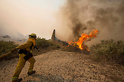 A firefighter rushes to extinguish the wildfire in the Naval Base at Point Mugu Friday, May 3, 2013..(AP Photo/Ringo H.W. Chiu)