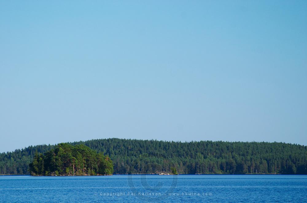 Blue lake with a small island under a bright blue summer sky. Lake Flen, Smaland region. Sweden, Europe.