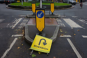 Confusing and contradiction of a diversion sign near a roundabout in East Dulwich, south London. We see an urban landscape of road markings and traffic instruction signs that disagree with each other - a detail of arrows that point in different directions that might confuse the driver and pedestrian.