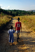 Two war orphan children walking back to their home in Ruyigi, Burundi. The ethnic violence in 1994 saw massacres of thousands and a whole generation of children are oprhans who have to live by themselves and bring up siblings.