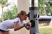 11 year old child looking through submarine periscope. USS Bowfin Submarine Museum and Park, part of the USS Arizona Memorial Museum in Pearl Harbour, Hawai.