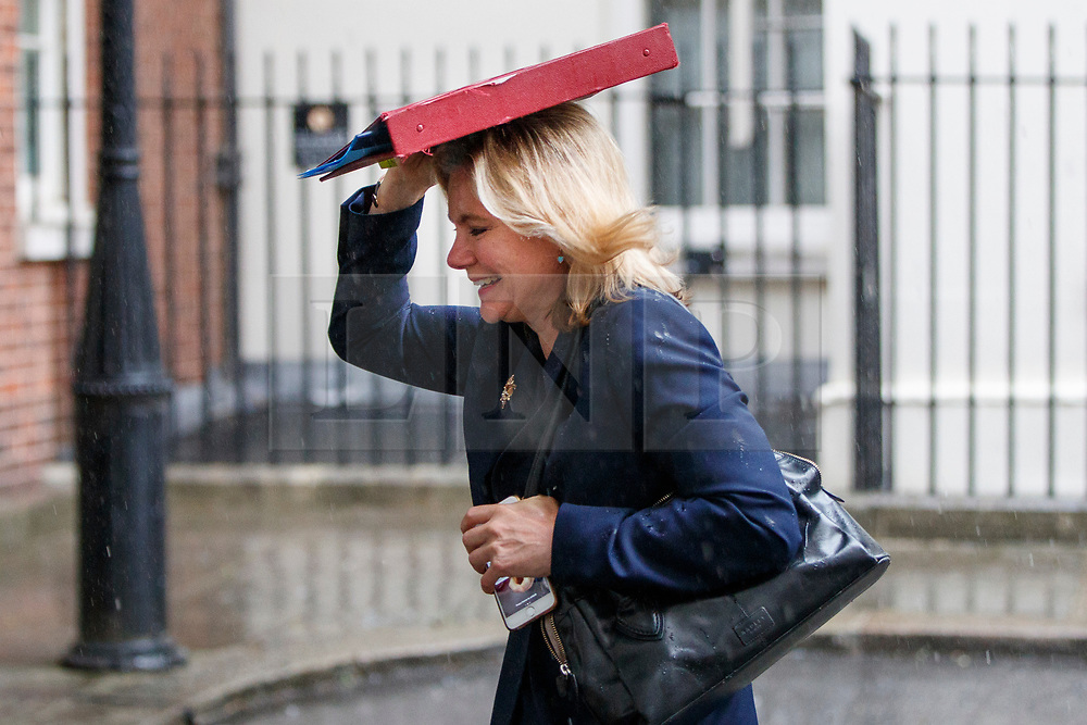 © Licensed to London News Pictures. 27/06/2017. London, UK. Education Secretary JUSTINE GREENING gets caught in the rain whilst leaving a cabinet meeting in Downing Street and uses her ministerial folder to take shelter in London on Tuesday, 27 June 2017. Photo credit: Tolga Akmen/LNP