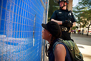 A protester and a police officer watch as members of the KKK arrive for a rally. Hundreds of counter protesters, including the Nation of Islam, New Black Panthers, and Huey Newton Gun Club, American Indian Movement, and ANTIFA gathered in downtown Dayton, Ohio to protest members of the Honorable Sacred Knights - a Ku Klux Klan group from Indiana. There were no arrests, and the protests ended peacefully as hundreds of police worked to keep the event peaceful and the protesters separated. Much of downtown Dayton was shutdown, and the courthouse square, where the KKK gathered, was surrounded by fence. Members of the KKK were given a police escort to the site, where about a dozen of them gathered, and then a police escort to safety.