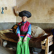 A portrait of a Pumi ethnic minority woman wearing her traditional clothing in her home, Lin Chang village, Yunnan Province, China. Costume styles in the past were identified by discrete regions and sub regions, but due to a number of factors some groups are more widely dispersed.  This may be due to migration or search for land, and more recently, as a result of re-settlement of groups by the Chinese government, made necessary by the construction of new roads, reservoirs and hydroelectric schemes. The People's Republic of China recognises 55 ethnic minority groups in China in addition to the Han majority. The ethnic minorities form 9.44% of mainland China and Taiwan's total population and the greatest number can be found in Yunnan Province, 34% (25 ethnic groups).