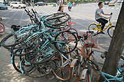 Bikes stacked on the pavement in Beijing<br /><br />Bike sharing in China has multiplied over the years with various brands offering shared bikes which can be unlocked using an application on your mobile telephone, and then locked and left anywhere for the next rider. Ofo and Mobike are the two world leaders. One of the problems is the huge over supply of bikes, which has meant many startups going out of business, and huge bike cemeteries created on the outskirts of China's mega cities, where hundred's of thousands of bikes are rusting away.