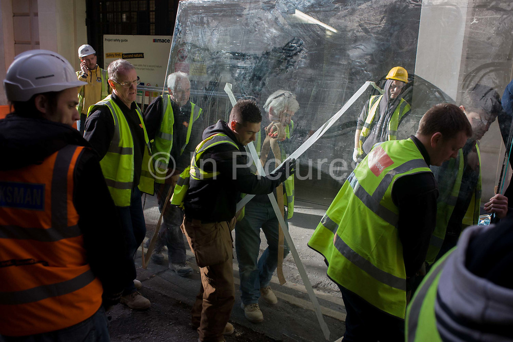 A team of labourers wearing hi-visibility tabards with the name of construction company Barnwood on the back, struggle to manhandle a very heavy plate-glass window through a City of London street. With tape that is crossed to avoid accidents, the glass is carried by the team of men in a narrow (medieval) side-street in the heart of the capital's financial district otherwise known as the Square Mile, after its circling Roman wall.