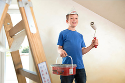 Young boy painting decorating room happy