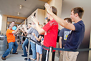 "12 JUNE 2009 -- SCOTTSDALE, AZ: Employees of the new Apple Store in Scottsdale, AZ, run through the line of shoppers sharing ""high fives"" with them before the store opened Friday. The outlet will be Arizona's largest Apple Store, occupying nearly 10,000 square feet in the Outdoor Lifestyle Center in the Scottsdale Quarter. The store, the fifth in the Phoenix area, uses a radically different design from other Apple Stores in some respects. Ceilings in the building are approximately 20 feet high, and lined with a 75-foot long skylight, reducing dependence on artificial lighting. Aiding the skylight is an all-glass front and rear, permitting visitors to see directly through the store. More than one thousand people lined to get into the store during the grand opening. Photo by Jack Kurtz"
