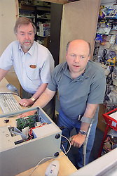 Man with disability and colleague repairing computer,