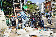 01 DECEMBER 2013 - BANGKOK, THAILAND: Thai anti-government protestors tear down a police barricade in Bangkok. Thousands of anti-government Thais confronted riot police at Phanitchayakan Intersection, where Rama V and Phitsanoluk Roads intersect, next to Government House (the office of the Prime Minister). Protestors threw rocks, cherry bombs, small explosives and Molotov cocktails at police who responded with waves of tear gas and chemical dispersal weapons. At least four people were killed at a university in suburban Bangkok when gangs of pro-government and anti-government demonstrators clashed. This is the most serious political violence in Thailand since 2010.    PHOTO BY JACK KURTZ