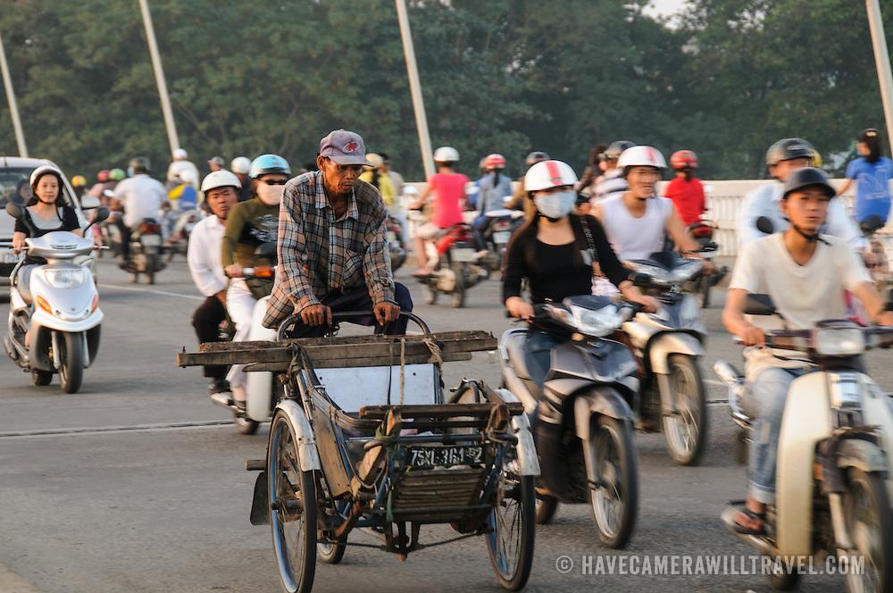 A man rides an old rickshaw bicycle through evening traffic on Cau Phu Xuan in Hue, Vietnam.