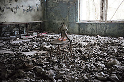 April 19, 2016 - Chernobyl - A doll with a gas mask in a deserted school in Pripyat city near Chernobyl, Ukraine. Chernobyl, a place replete with horrific memories in northern Ukraine, close to Belarus, is now open to tourists, almost 30 years to the date after a nuclear power plant there exploded. It was the worst nuclear accident in human history. A large tract of land around the plant was designated a forbidden zone and ordinary people were completely prohibited from entering after the disaster occurred on April 26, 1986. The accident released more than 8 tons of radioactive leaks, directly contaminated an area of over 60,000 square kilometers and exposed some 3.2 million people to dangerous levels of radiation. (Credit Image: © Dai Tianfang/Xinhua via ZUMA Wire)