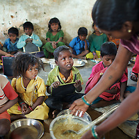 Congress Manjhi's son Pramod (centre), 3, and other children receive their midday meals in Mananbigha village Anganwadi (child care) centre.  ..Mananbigha resident and day-wage laborer, Congress Manjhi died of hunger in April 2010. He was a landless Maha Dalit (Bhuiyan caste). He had tuberculosis. Bedridden, he had been unable to work for four years. As a consequence, Congress' wife, Kari Devi, 35, became the sole breadwinner for their family of four children. When Kari Devi was bitten by a dog in 2010, she was not able to work for 15 days. She had to travel 40km for a rabies vaccination as the local hospital in Barachatti was out of stock. This incurred substantial expense at a time when no one in the family was bringing in an income. Kari Devi had to borrow money for treatment. The family had not been granted a BPL (Below Poverty Line) card even thought they were entitled to one. As a consequence they had no access to rations from the PDS (Public Distribution System). With no food, Congress Manjhi eventually succumbed to tuberculosis. Following his death, it took representation from the Oxfam-supported Nyadal, a local village court, to force the administration into granting Kari Devi the 25kg of grains to which she and her family are entitled as part of the Antyodaya scheme (providing staple food for the poorest of the poor). Kari Devi must now bring up her four children alone. She is a member of the local five-person vigilance committee that reports to the Nyadal...Like much of rural Bihar state - particularly among low caste communities - the residents of Mananbigha regularly go hungry. Some have died as a result of food shortages. There is a scarcity of water in the area and no irrigation facility. Though there are schemes in place to support vulnerable families, it is an ongoing struggle for residents to claim benefits, including rations, that are by rights theirs. Oxfam partners have helped to promote awareness of social security schemes among residents in Ma