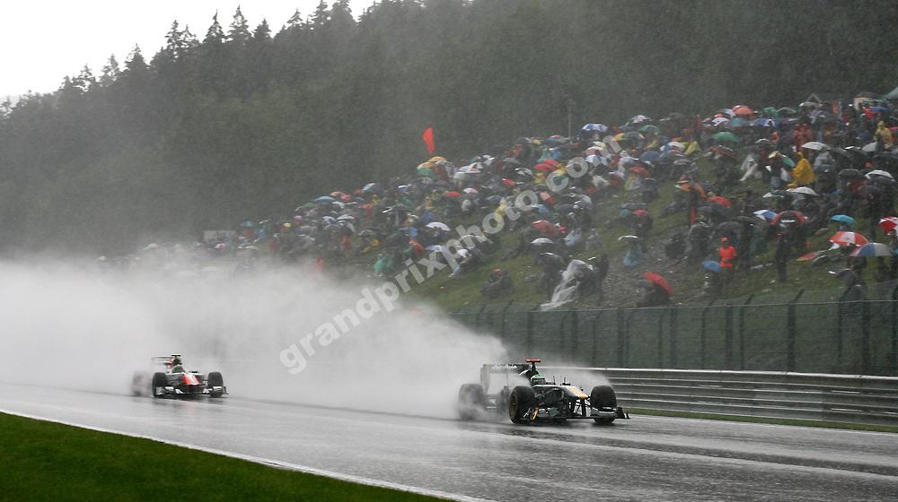 Heikki Kovalainen (Team Lotus-Renault) with Vitantonio Liuzzi (HRT-Cosworth) in heavy rain at the 2011 Belgian Grand Prix at Spa-Francorchamps. Photo: Grand Prix Photo