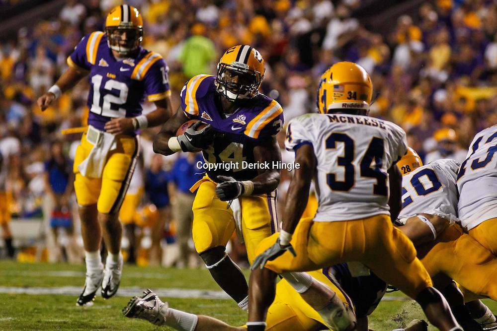 October 16, 2010; Baton Rouge, LA, USA; LSU Tigers running back Stevan Ridley (34) runs as McNeese State Cowboys safety Malcolm Bronson (34) pursues during the first half at Tiger Stadium.  Mandatory Credit: Derick E. Hingle