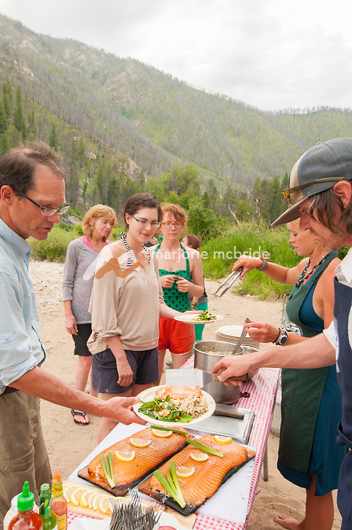 Guides serving Salmon dinner at Sheepeater Camp, Middle Fork of the Salmon River, Idaho.