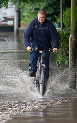 © Licensed to London News Pictures 18/06/2021. Aylesford, UK. A young man getting wet riding his bike in Aylesford, Kent. Torrential rain is causing roads to flood in Kent as thunderstorms are set to hit the UK again today. Photo credit:Grant Falvey/LNP