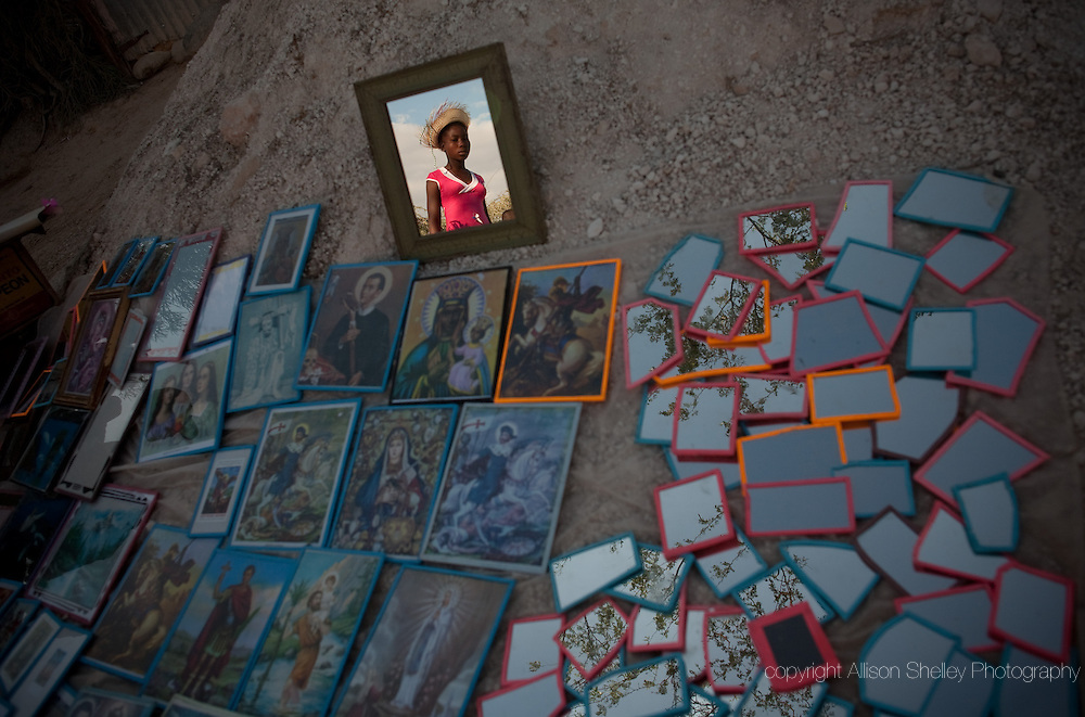 A girl is reflected in a mirror for sale by a vendor along the path visitors attend the annual Good Friday pilgrimage, visiting the stations of the cross while climbing Kalvé Mirak (Calvary Miracle) in Ganthier, about 35 miles northwest of Port-au-Prince, Haiti, April 2, 2010.