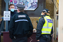 Portobello, Scotland, UK. 10 January 2020. Despite a national lockdown currently enforced in Scotland, Portobello promenade and beach was busy with large numbers of people spending Sunday afternoon there. Several police patrols were evident mostly keeping low key but officers spoke to cafe owners to urge them to keep correct social distancing between customers. Pic; Police speak to manager of cafe to explain social distancing.  Iain Masterton/Alamy Live News