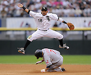 CHICAGO - SEPTEMBER 28:  Orlando Cabrera #18 of the Chicago White Sox leaps over a sliding Jamie Carroll #7 to turn a double play during the game against the Cleveland Indians at U.S. Cellular Field in Chicago, Illinois on September 28, 2008.  The White Sox defeated the Indians 5-1.  (Photo by Ron Vesely)