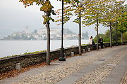 Two women sit and chat along the road into Orta San Giulio, with Lake Orta and its famous island in the distance, Italy.