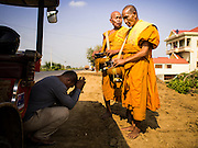 27 FEBRUARY 2015 - PONHEA LEU, KANDAL, CAMBODIA:  A tuk-tuk driver stops to pray and make an alms donation to Buddhist monks in Kandal province, Cambodia. Cambodian tuk-tuks are three wheeled taxis pulled by motorcycle.   PHOTO BY JACK KURTZ