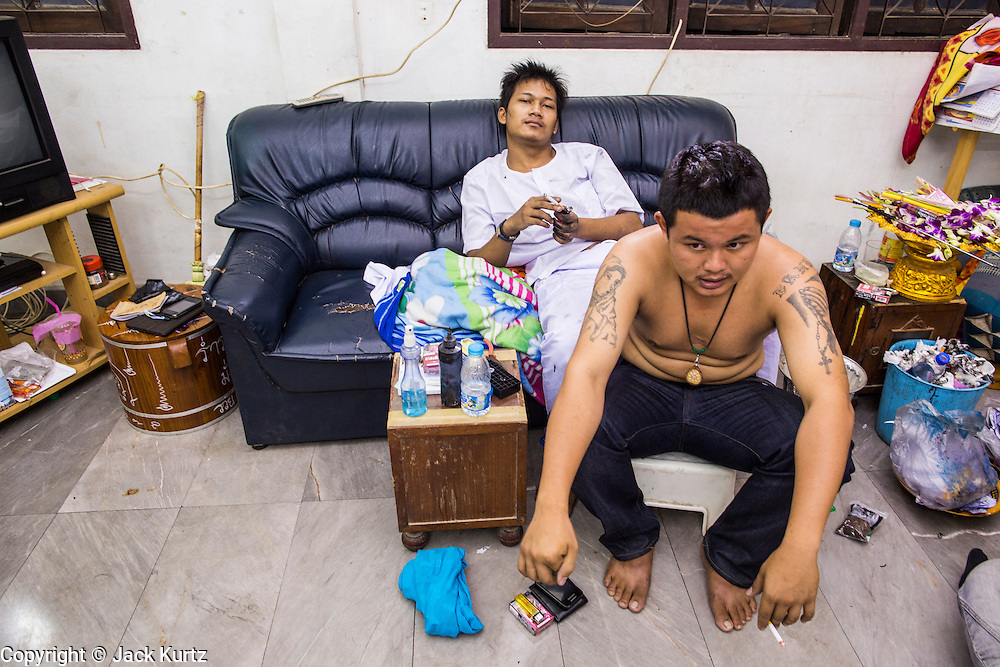 "22 MARCH 2013 - NAKHON CHAI SI, NAKHON PATHOM, THAILAND: A tattooist and his client take a break during a lengthy Sak Yant tattoo at Wat Bang Phra. Wat Bang Phra is the best known ""Sak Yant"" tattoo temple in Thailand. It's located in Nakhon Pathom province, about 40 miles from Bangkok. The tattoos are given with hollow stainless steel needles and are thought to possess magical powers of protection. The tattoos, which are given by Buddhist monks, are popular with soldiers, policeman and gangsters, people who generally live in harm's way. The tattoo must be activated to remain powerful and the annual Wai Khru Ceremony (tattoo festival) at the temple draws thousands of devotees who come to the temple to activate or renew the tattoos. People go into trance like states and then assume the personality of their tattoo, so people with tiger tattoos assume the personality of a tiger, people with monkey tattoos take on the personality of a monkey and so on. In recent years the tattoo festival has become popular with tourists who make the trip to Nakorn Pathom province to see a side of ""exotic"" Thailand. The 2013 tattoo festival was on March 23.    PHOTO BY JACK KURTZ"