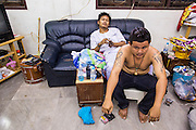 """22 MARCH 2013 - NAKHON CHAI SI, NAKHON PATHOM, THAILAND: A tattooist and his client take a break during a lengthy Sak Yant tattoo at Wat Bang Phra. Wat Bang Phra is the best known """"Sak Yant"""" tattoo temple in Thailand. It's located in Nakhon Pathom province, about 40 miles from Bangkok. The tattoos are given with hollow stainless steel needles and are thought to possess magical powers of protection. The tattoos, which are given by Buddhist monks, are popular with soldiers, policeman and gangsters, people who generally live in harm's way. The tattoo must be activated to remain powerful and the annual Wai Khru Ceremony (tattoo festival) at the temple draws thousands of devotees who come to the temple to activate or renew the tattoos. People go into trance like states and then assume the personality of their tattoo, so people with tiger tattoos assume the personality of a tiger, people with monkey tattoos take on the personality of a monkey and so on. In recent years the tattoo festival has become popular with tourists who make the trip to Nakorn Pathom province to see a side of """"exotic"""" Thailand. The 2013 tattoo festival was on March 23.    PHOTO BY JACK KURTZ"""